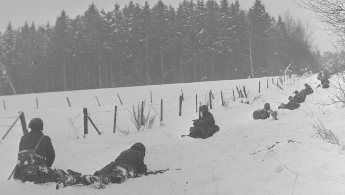Members of the 30th Infantry Division crawl prone while crossing open terrain near Pont, Belgium. (Co. E, 2nd Bn.) 1/17/45