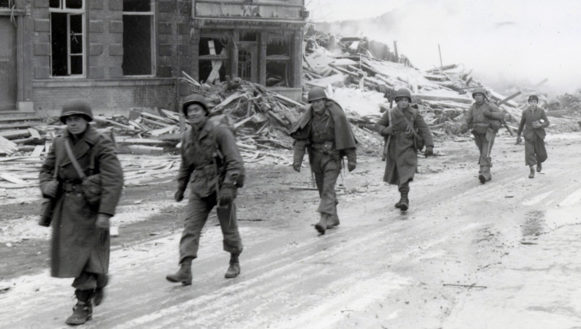 Troops of the 30th Infantry Division march through Malmedy which was leveled in error by U.S. bombers, 29th December 1944