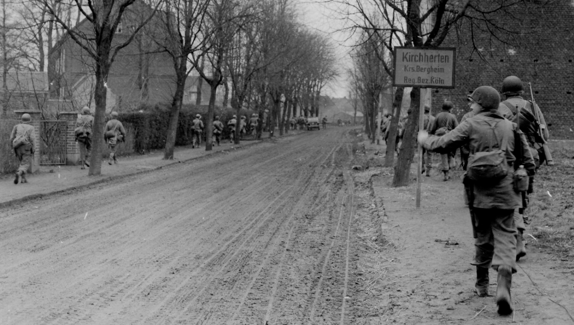 Troops of Co. L, 119th Infantry Regiment, 30th Infantry Division, moving through Kirchherten, 27 February 1945