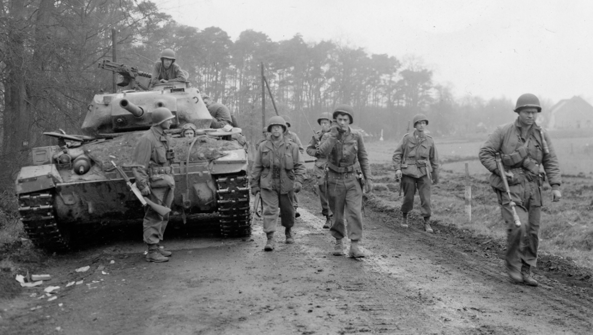 Troops of 1st Battalion, 120th IR, 30th Infantry Division, moving through Wesel Forest area in pursuit of fleeing 116th Panzer Div., March 1945